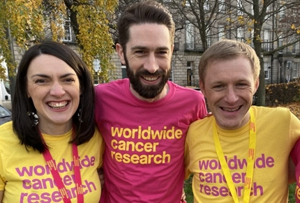 Three smiling people in Worldwide Cancer Research t-shirts